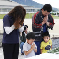 A family offers prayers to the victims of the 1991 pyroclastic flow from Mount Unzen on the 28th anniversary of the disaster Monday in Shimabara, Nagasaki Prefecture. | KYODO