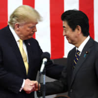 U.S. President Donald Trump shakes hands with Prime Minister Shinzo Abe aboard the Maritime Self-Defense Force's Kaga helicopter carrier in Yokosuka, Kanagawa Prefecture, on May 28. | REUTERS