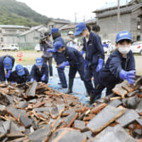Student volunteers sort through a pile of broken roof tiles on Monday in Tsuruoka, Yamagata Prefecture, after the area was shaken by a strong earthquake last week. | KYODO