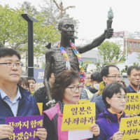Protesters call for an apology and compensation by Japan over wartime labor on May 1 in Busan, South Korea, in front of a statue symbolizing Korean wartime laborers. | KYODO