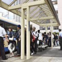 Commuters form a long line at a bus stop at Shin-Sugita Station in Yokohama on Monday morning, as train services on the Kanazawa Seaside Line remain suspended. An accident involving an unmanned train occurred at the station on Saturday evening. | KYODO