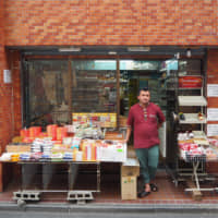 General store: Jeevan Budhathoki stands in front of Everest Spice & Halal Food, which sells authentic Nepalese groceries and offers a money transfer service to Nepal. | KYODO