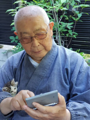 A couple of pals: The head priest of Kairyuji temple on Shiraishi Island checks an electronic dictionary while his new furry friend, a stray kitten, watches from his arms. | AMY CHAVEZ