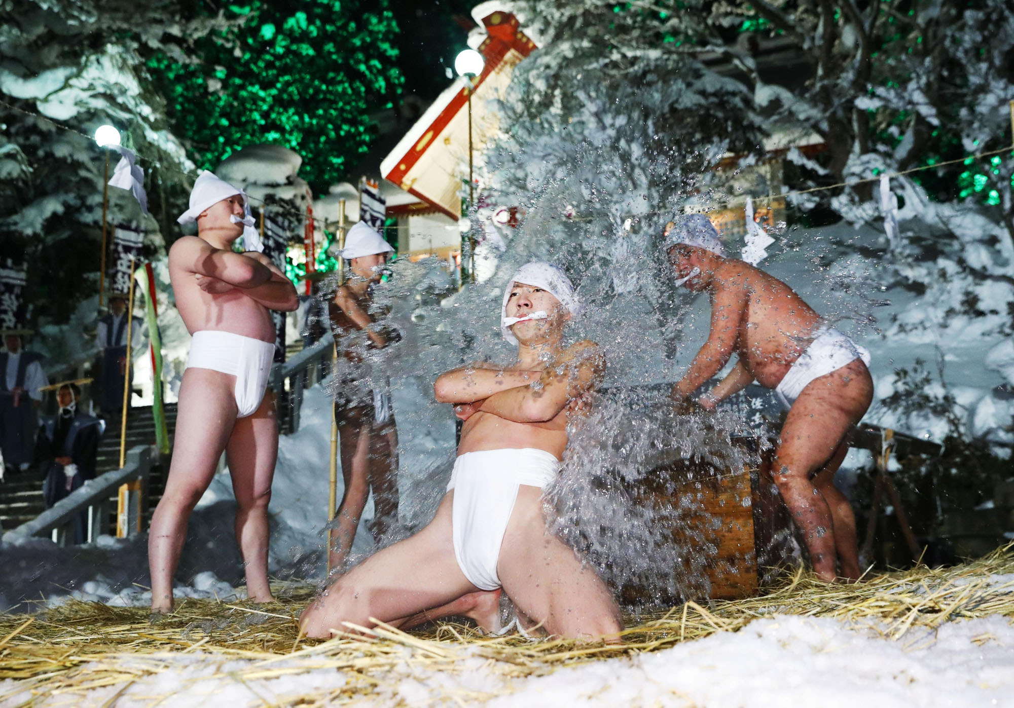 Four men splash cold water over each other in temperatures of minus 5 Celsius during a Shinto ritual dating back to 1831 to pray for bumper fish and farm crops at a shrine in Kikonai, Hokkaido, in January 2017. | KYODO