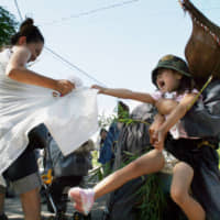 A child screams as a man tries to separate her from her mother during the Yokkabui Festival at Tamate Shrine in Minamisatsuma, Kagoshima Prefecture, in August 2007. | KYODO