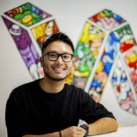 Walls of color: Jun Arita with one of his murals commissioned for the Skinnies studio space in Auckland | TODD PACEY