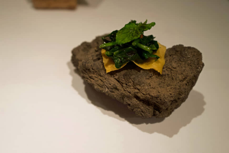 Satoyama gastronomy: Spinach and sea urchin presented on basalt carried down from the slopes of Mount Fuji. | OSCAR BOYD