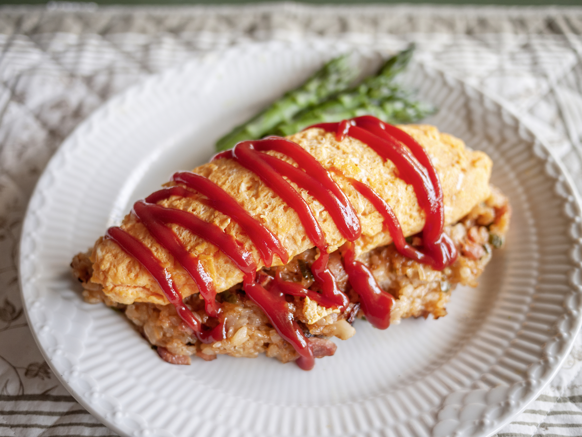 Just as film director Juzo Itami ordered: In this omurice (rice omelette), a pile of chicken stir-fried rice is topped with a soft-set omelette and tangy ketchup. | MAKIKO ITOH