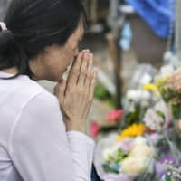 A woman prays at the site of a mass stabbing on June 4, a week after the incident in which a knife-wielding man killed two and injured more than 15 people near a bus stop in Kawasaki. | KYODO