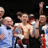 Kazuto Ioka (center) celebrates in the ring after his victory over Aston Palicte for the vacant WBO super flyweight championship on Wednesday night at Makuhari Messe in Chiba. The victory made Ioka the first Japanese man to win world titles in four different weight classes. | KYODO