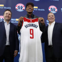 Wizards first-round draft choice Rui Hachimura displays his new jersey at an introductory news conference on Friday between coach Scott Brooks (left) and interim general manager Tommy Sheppard in Washington. | AP