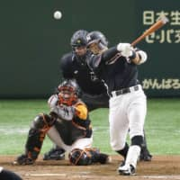 The Marines' Shogo Nakamura hits a go-ahead single in the ninth inning against the Giants on Saturday afternoon at Tokyo Dome. Chiba Lotte beat Yomiuri 6-5. | KYODO
