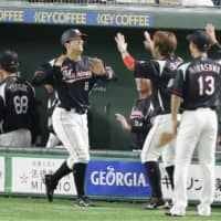 Chiba Lotte's Shogo Nakamura is congratulated by teammates moments after hitting a tiebreaking single in the ninth. | KYODO