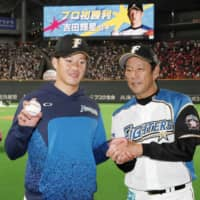 Hokkaido Nippon Ham rookie pitcher Kosei Yoshida poses with Fighters manager Hideki Kuriyama after earning the first win of his career on Wednesday at Sapporo Dome.   KYODO