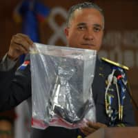 The director of the National Police, Gen. Ney Aldrin Bautista Almonte, shows the weapon that was used to shoot former Boston Red Sox slugger David Ortiz, during a press conference at the Attorney General's Office in Santo Domingo Wednesday. Six suspects, including the alleged gunman, have been detained in the shooting, the Dominican Republic's chief prosecutor said Wednesday. | AP