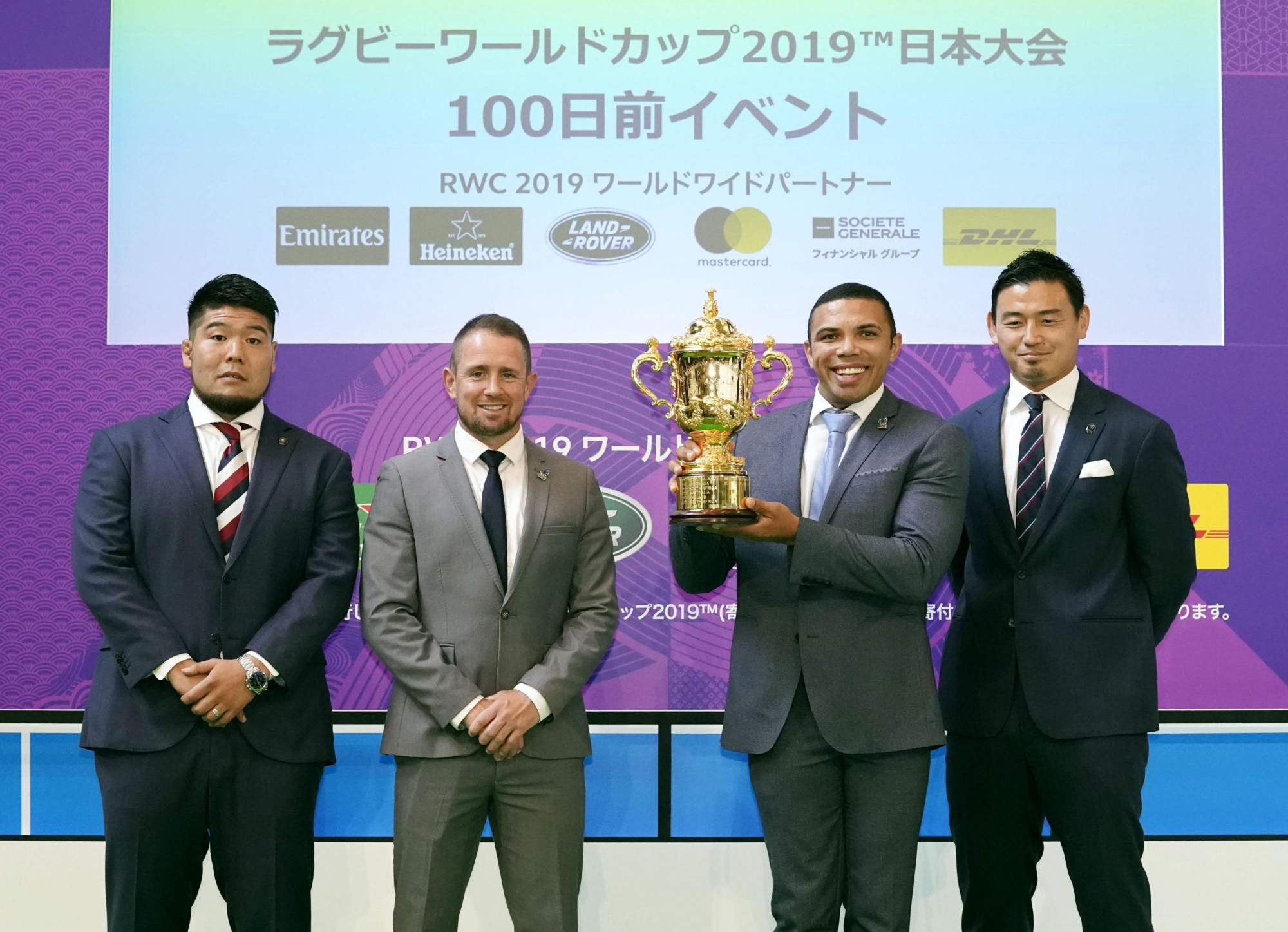 Former South Africa player Bryan Habana (second from right) holds the Webb Ellis Cup alongside (from left) Kensuke Hatakeyama, former Wales international Shane Williams and Ayumu Goromaru during a Rugby World Cup countdown event on Wednesday in Tokyo. | KYODO
