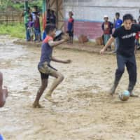 Makoto Hasebe plays soccer with Rohingya children on a muddy field at the Kutupalong refugee camp on Thursday. | KYODO
