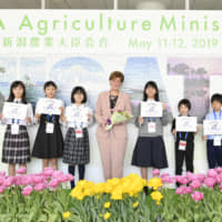 Canadian Agriculture and Agri-Food Minister Marie-Claude Bibeau with local children in front of a panel at the entrance of the event venue.