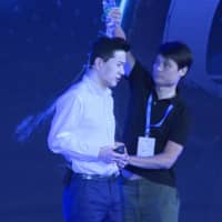A man pours water on Baidu co-founder and CEO Robin Li during a presentation in Beijing on Wednesday. | AFP-JIJI