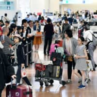 Travelers crowd Haneda airport in Tokyo on May 5 during Golden Week. | KYODO