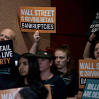 An attendee holds up a 'Wall Street Is Driving Retail Bankruptcies' sign during a news conference on the Stop Wall Street Looting Act on Capitol Hill in Washington July 18. Sen. Elizabeth Warren's plan would make private-equity firms responsible for debts and retirement pension obligations of companies they purchase, while making their profits contingent on the success of the entities they control. | BLOOMBERG