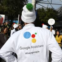 Attendees wait to ask a question of a Google Assistant at a giant 'Hey Google' gumball machine game at CES 2019, at the Las Vegas Convention Center in Las Vega in January. | AFP-JIJI