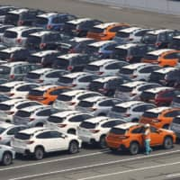 Cars await shipment at a port in Kawasaki. The government has cut its economic growth forecast for fiscal 2019, citing weak exports caused mainly by a slowdown in demand from China.   KYODO