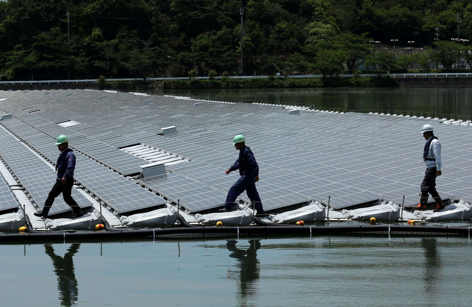 Workers walk past rows of panels at a floating solar power station in Kasai, Hyogo Prefecture.   BLOOMBERG