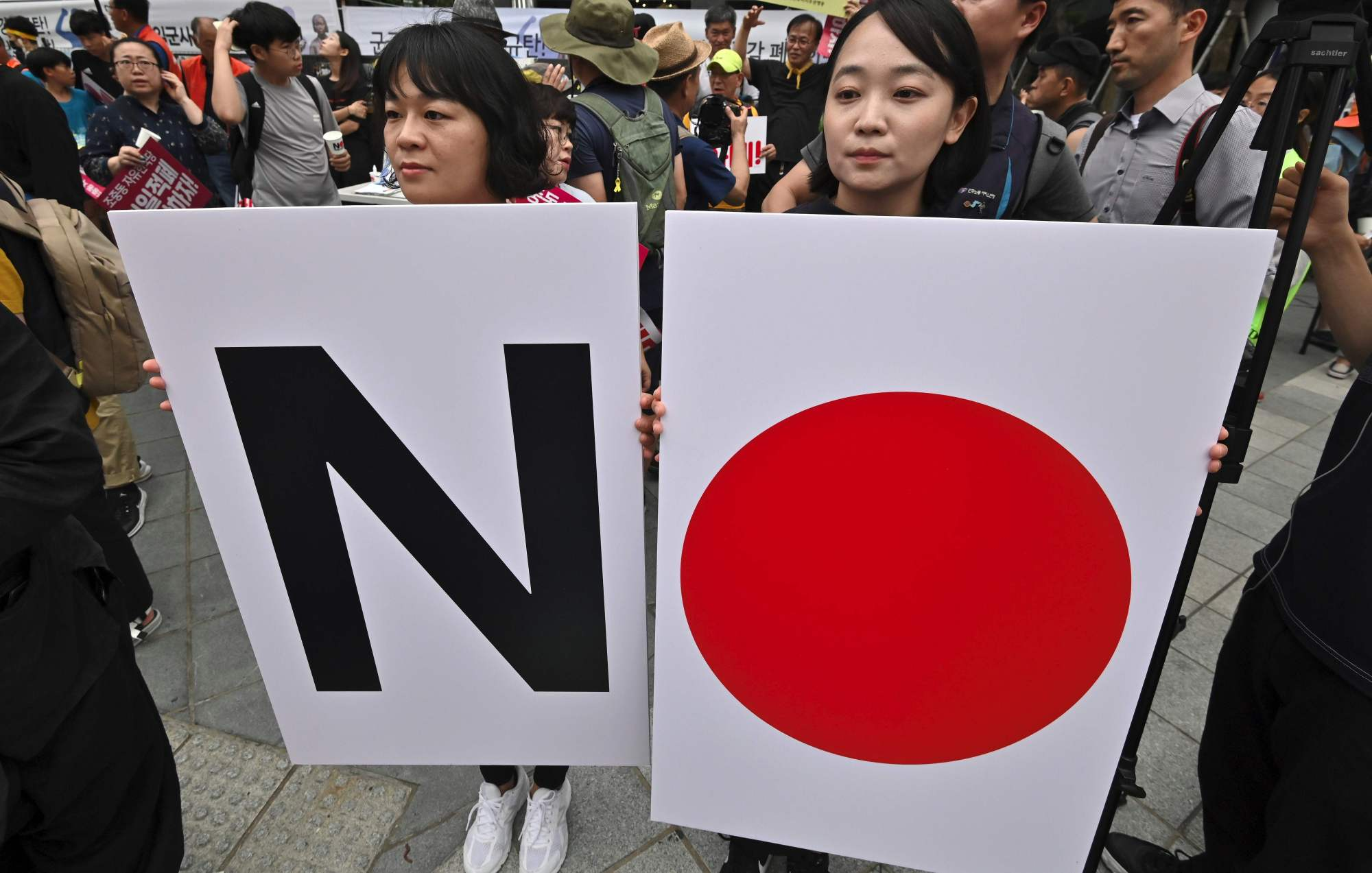 South Korean protesters hold placards that play on the Hinomaru during a rally in Seoul on July 20. | AFP-JIJI