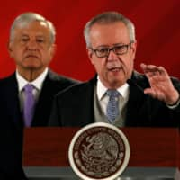 Mexican Finance Minister Carlos Urzua speaks as President Andres Manuel Lopez Obrador looks on during a news conference to announce a plan to strengthen finances of state oil firm Pemex, at the National Palace in Mexico City in February. | REUTERS