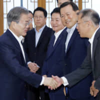 South Korean President Moon Jae-in shakes hands with Chung Eui-sun, chief vice chairman of Hyundai Motor Group, during a meeting with executives from South Korea's top 30 conglomerates at the Presidential Blue House in Seoul on Wednesday. | REUTERS