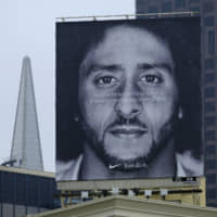 A large billboard stands on top of a Nike store showing former San Francisco 49ers quarterback Colin Kaepernick, at Union Square in San Francisco last fall. Nike is pulling a flag-themed tennis shoe after Kaepernick complained to the shoemaker, according to the Wall Street Journal. | AP