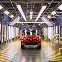 Captur crossover SUVs move down the assembly line at a Renault automobile plant in Moscow in May. Renault's troubled ties with Nissan are hurting its earnings. | BLOOMBERG