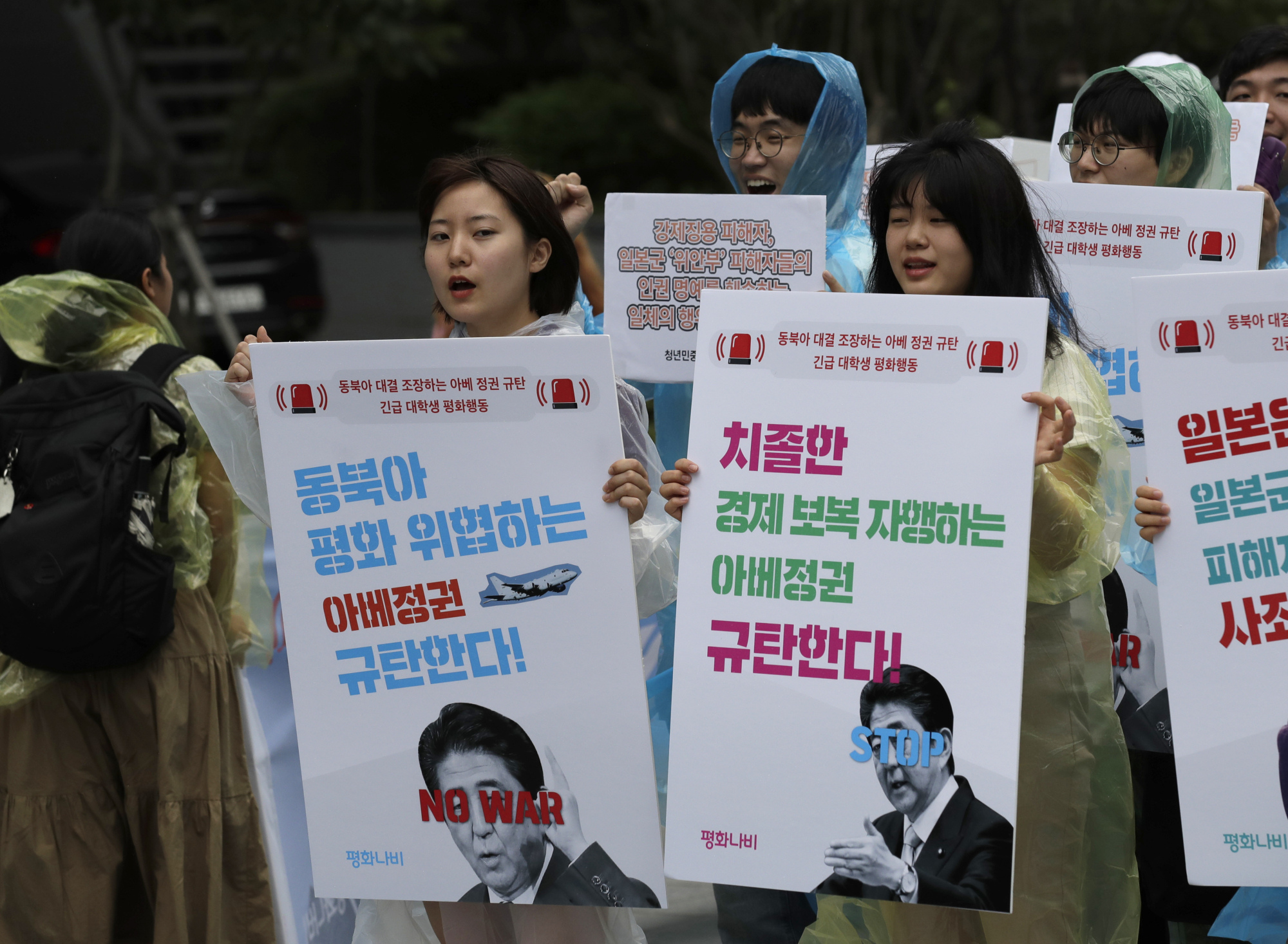 South Korean students shout slogans as they march to denounce the Japanese government's decision to impose some restrictions on exports, near the Japanese Embassy in Seoul on Wednesday. | AP