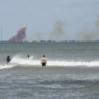 A cloud of orange smoke rises over nearby Cape Canaveral Air Force Station, as seen from Cocoa Beach, Florida, in April after the SpaceX Dragon 2 capsule was destroyed during a test. SpaceX says a leaky valve caused its crew capsule to explode during the test back in April. The company announced the preliminary results of its accident investigation Monday.   CRAIG BAILEY / FLORIDA TODAY / VIA AP