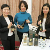 Okinawa tourism officials display bottles of awamori, a rice-based distilled spirit, in the Japanese Embassy in London in November 2016. | KYODO