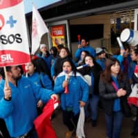 Demonstrators with a placard that reads 'No more abuses' take part in a protest during a strike of workers of the retailer Walmart demanding better wages and working conditions, in Santiago Wednesday. | REUTERS