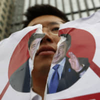 A protester holds a defaced image of Prime Minister Shinzo Abe during a rally denouncing the Japanese government's decision on their exports to South Korea in front of the Japanese Embassy in Seoul on Wednesday. | AP