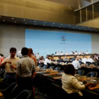Delegates arrive for the meeting before the General Council at the World Trade Organization in Geneva on Wednesday to discuss the worsening trade and diplomatic dispute between South Korea and Japan. | REUTERS