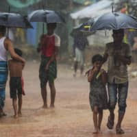 Rohingya refugees shelter under umbrellas as they walk along a path during monsoon rainfall at the Kutupalong refugee camp in Ukhia on Tuesday. | AFP-JIJI
