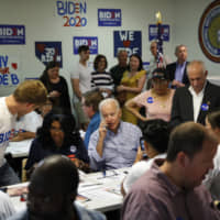 Former Vice President and Democratic presidential candidate Joe Biden speaks on the phone during a campaign phone bank event an electrical workers union hall Saturday in Las Vegas. | AP