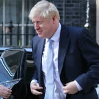Britain's new prime minister, Boris Johnson, arrives back at 10 Downing Street in London Wednesday. Johnson took charge Wednesday, on a mission to deliver Brexit by Oct. 31 with or without a deal. | AFP-JIJI