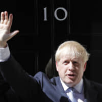 Britain's new prime minister, Boris Johnson, waves from the steps outside 10 Downing Street in London, Wednesday. | AP