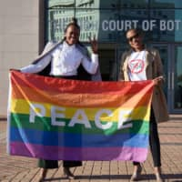 Activists hold the rainbow flag as they celebrate outside the Botswana High Court in Gaborone on June 11. The country's attorney general said Friday that the government will appeal last month's landmark high court ruling that decriminalized homosexuality. | AFP-JIJI