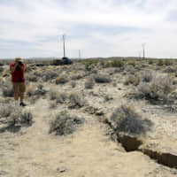 A visitor takes a photo Sunday of a crack on the ground following recent earthquakes, outside of Ridgecrest, California.   AP