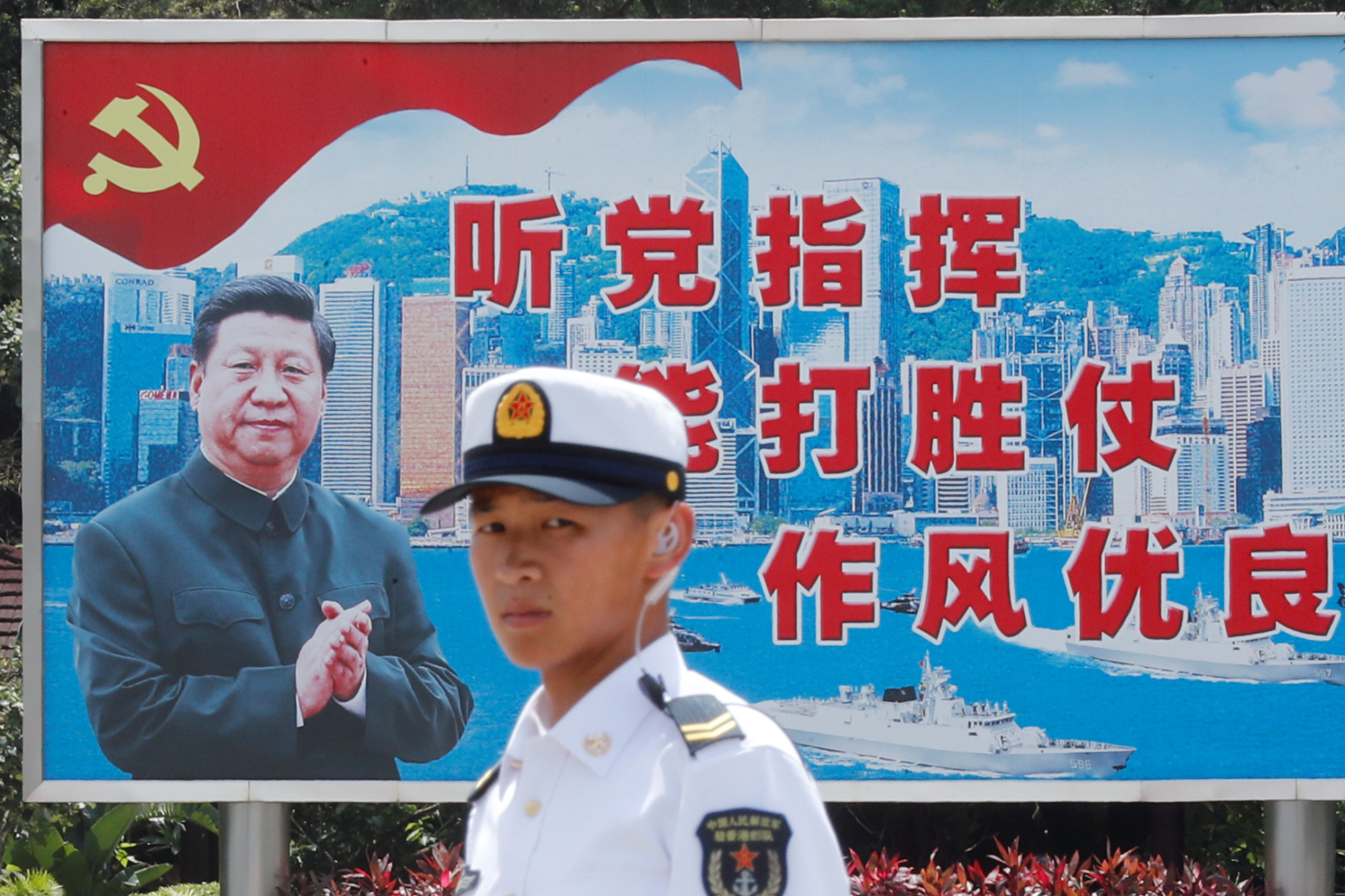 A Chinese People's Liberation Army Navy soldier stands in front of a backdrop featuring Chinese President Xi Jinping during an open day of Stonecutters Island naval base in Hong Kong on June 30.   REUTERS