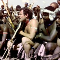 A 1989 photo taken in Keate's Drift, South Africa, shows Johnny Clegg (center), leader of the pop group Savuka, in a traditional Zulu outfit during his wedding with Jennifer Bartlett. | AFP-JIJI