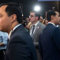 Democratic presidential hopeful former Housing and Urban Development Secretary Julian Castro (right) and his twin brother, U.S. Rep. Joaquin Castro, Democrat of Texas, speak with the press in the Spin Room after participating in the first Democratic primary debate of the 2020 presidential campaign season hosted by NBC News at the Adrienne Arsht Center for the Performing Arts in Miami June 26. | AFP-JIJI