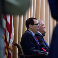 Steven Mnuchin, U.S. Treasury secretary (left), and Charles Rettig, commissioner of the Internal Revenue Service (IRS), listen during an IRS Criminal Investigation 100th year anniversary event at the IRS headquarters in Washington on Monday. | BLOOMBERG