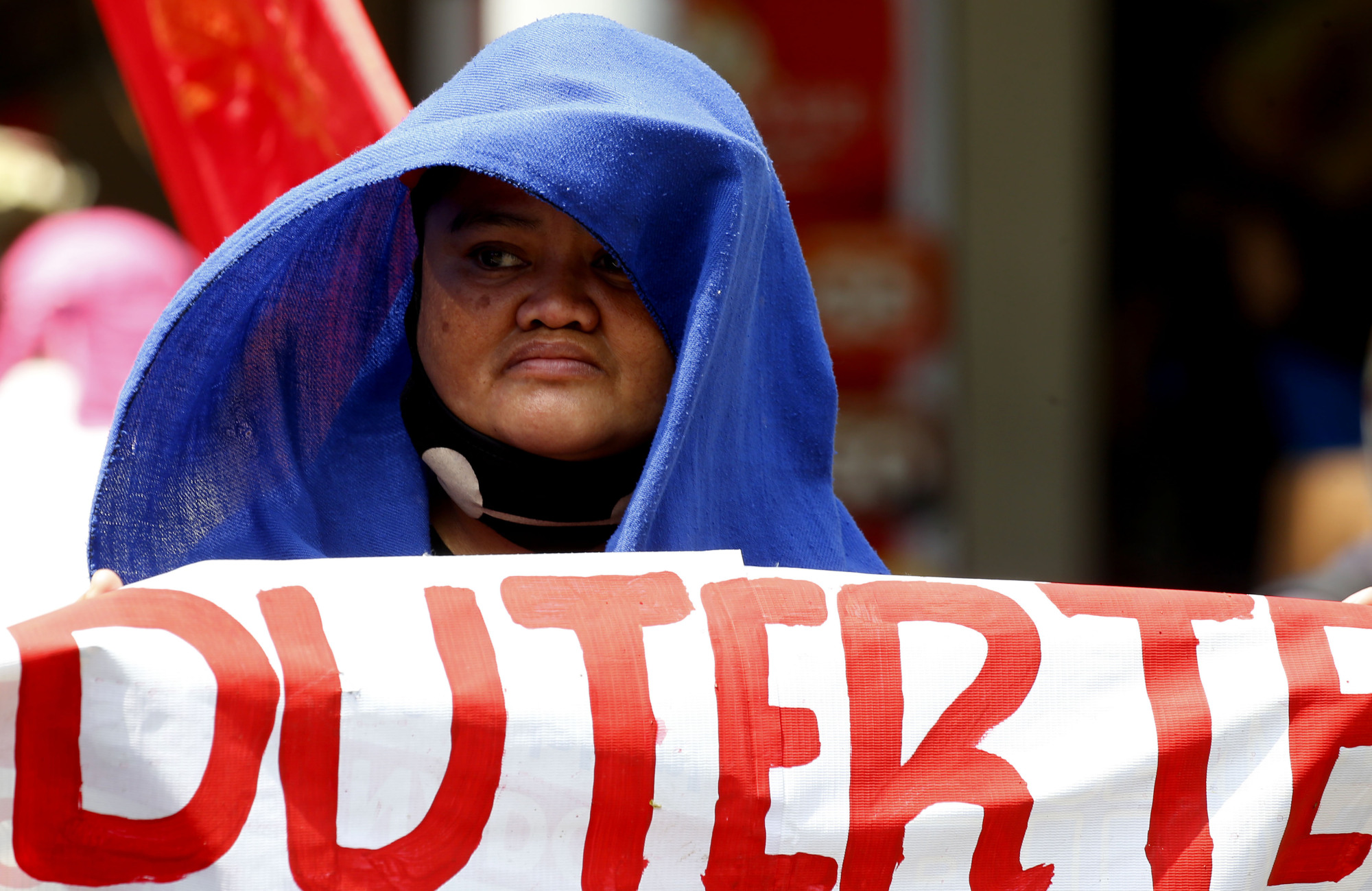 A protester displays a sign during a rally near the presidential palace in Manila on Friday to call for the impeachment of President Rodrigo Duterte. | AP